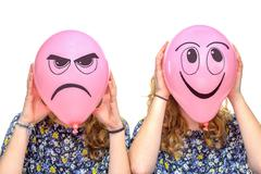Two girls holding pink balloons with facial expressions Stock Photos