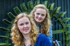 Two dutch teenage girls in front of water mill - stock photo