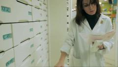 Good looking Pharmacist woman taking medicine from a drawer Stock Footage