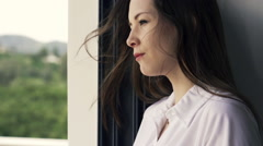 Pensive woman standing by window at home, slow motion shot at 240fps HD Stock Footage