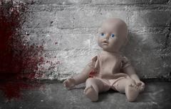 Concept of child abuse - Bloody doll - stock photo