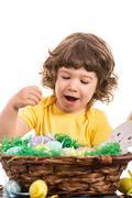 Amazed toddler choose Easter egg - stock photo