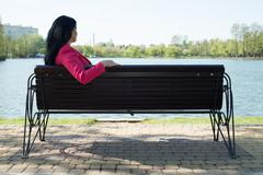 Solitude woman on bench in park - stock photo