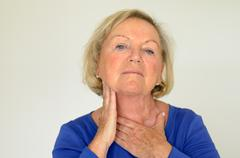 Thoughtful elderly woman with her hand to her neck - stock photo