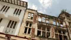 Newest building facade next to ruined colonial house front wall, looking up Stock Footage