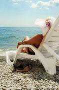 Closeup view on lady in chaise-longue at the coast of sea - stock photo
