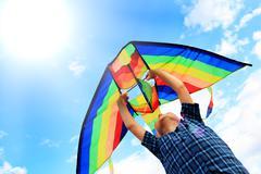 Llittle boy flies a kite in the sky Stock Photos