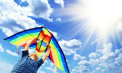 Happy child flies a kite in the sky - stock photo