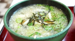 Detail view of Udon soup with tempura topping in green bowl Stock Footage