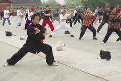 People practice tai chi chuan gymnastics in Beijing, China. Kuvituskuvat
