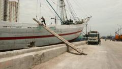 Cargador climb up gang-board to wooden Pinisi vessel, old port of Jakarta city Stock Footage