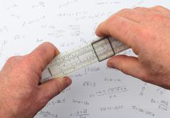 Person calculating on a slide ruler Stock Photos