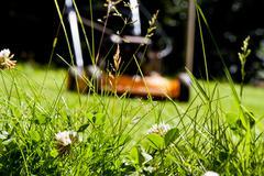 Lawn mower seen thrugh grass - stock photo