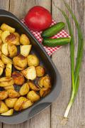 Fried potatoes in the pan on the aged wooden table. Stock Photos