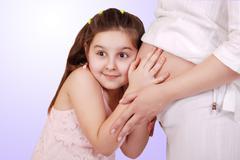 Daughter listen near pregnant mom tummy - stock photo