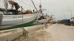 Dusty road in old port, traditional pinisi cargo boats, glide shot Stock Footage