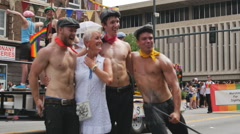 woman takes picture with shirtless performers in gay pride parade - stock footage