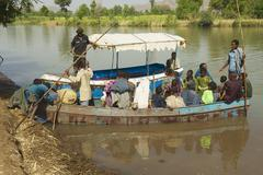Passengers cross river by local ferry boat, Bahir Dar, Ethiopia. - stock photo