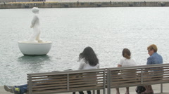 Relaxing in front of a statue floating on water in the old harbour of Barcelona Stock Footage