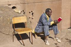 Stock Photo of Man reads book in Lalibela, Ethiopia.