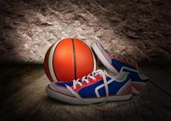 Colored mens sneakers with orange ball on dark background Stock Photos