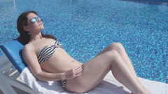 Female enjoying relax at beach, lying on sun lounger near water Stock Footage