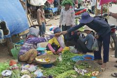 People sell vegetables at the local market, Siem Reap, Cambodia. - stock photo