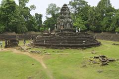 Tourists explore the Neak Pean temple in Angkor, Cambodia. - stock photo