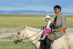 Mongolian man rides on horseback with a kid, Harhorin, Mongolia. Stock Photos