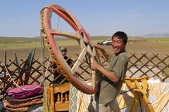 Mongolian man assembles yurt in steppe, circa Harhorin, Mongolia. - stock photo