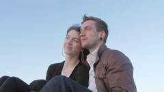 Boyfriend and girlfriend admire the view at sunset - stock footage