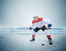 An aggresive hockey player on ice dribbling with puck - stock photo
