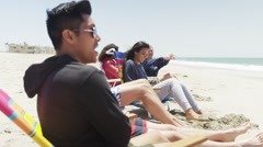 Young hip mixed ethnic friends sitting having fun at the beach - stock footage
