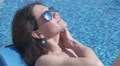 Seductive girl at poolside touching breasts, rubbing neck gently Footage