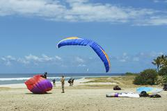 Paragliders land at the ocean shore, Reunion. - stock photo