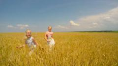 Children skipping through the field of wheat and rejoice. Stock Footage