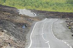 Curbed asphalt road over volcanic lava, Reunion island, France. - stock photo