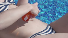 Closeup of female rubbing belly, applying sunblock oil, health Stock Footage