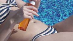 Closeup female hands rubbing belly, applying sunblock on skin Stock Footage