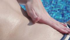 Extreme closeup of female hands applying suncream, rubbing belly Stock Footage