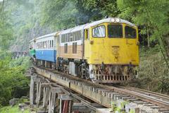 Vintage locomotive passes Death railway in Kanchanaburi, Thailand. Stock Photos
