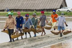 People work at the salt farm in Huahin, Thailand. - stock photo