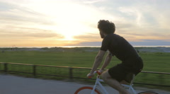 Athletic young man biking in the sunset Stock Footage