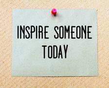 Inspire Someone Today  written on paper note pinned with red thumbtack - stock photo
