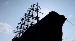 The silhouette of a large wooden ship with mast and sail against the sky Stock Footage