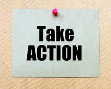 Take Action written on paper note pinned with red thumbtack on wooden board.  - stock photo