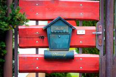 post box on red wooden gate - stock photo