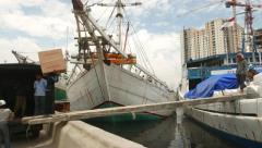 Loader picks up on his shoulders and carry box, old port of Jakarta Stock Footage