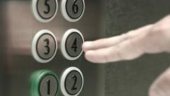 Man presses a button the fourth floor in an elevator Stock Footage