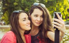 Two young women taking a selfie outdoors Stock Photos